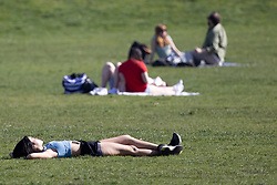 © Licensed to London News Pictures. 30/03/2021. London, UK. Members of the public relax in a sunny Greenwich Park in South East London. Temperatures are expected to rise with highs of 23 degrees forecasted for parts of London and South East England today . Photo credit: George Cracknell Wright/LNP