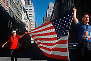 A week after the 9-11 terrorist attacks on the Twin Towers and the Pentagon, a couple cary the American flag down a lower-Manhattan street, on 21st September 2001, New York, USA.