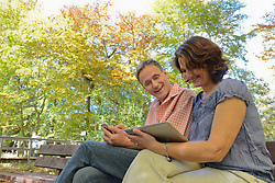 Couple sitting on bench and showing each other something on smart phone and digital tablet, Bavaria, Germany