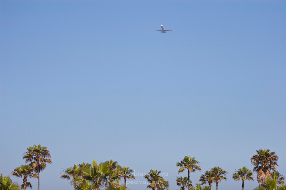 Airliner taking off from San Diego International Airport, over Ocean Beach.