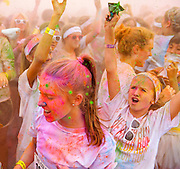 Participanta in charity 10K road race celebrate their finish by throwing packets of colorful powered dye into the air.
