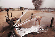 A worker from the Red Adair Company attempts to wash oil off his body after capping an oil well after they extinguished the fire. The burning Al Burgan oil fields in Kuwait after the end of the Gulf War in May of 1991 were covered in oil that rained down from the clouds of oil smoke and oil shooting into the air after a fire had been extinguished. More than 700 wells were set ablaze by retreating Iraqi troops creating the largest man-made environmental disaster in history.