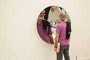 A man looks at his distorted reflection in a polished stainless steel mirror by Aneesh Kapoor in the Lisson Gallery.