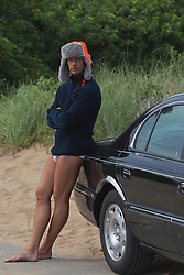 good looking man wearing a winter hat, sweater and underwear outdoors while leaning against a car