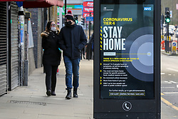 © Licensed to London News Pictures. 25/12/2020. London, UK. A couple walk past the government's 'Stay Home- Tier 4' publicity campaign poster in north London amid fears of a third national lockdown after Christmas as COVID-19 infection rates rise. Many more areas of England will go into Tier 4 restrictions from Boxing Day as the mutated strains continue to spread throughout England. Photo credit: Dinendra Haria/LNP