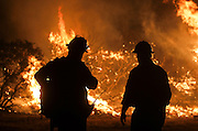 Firefighters watch the Blue Cut wildfire burning near Cajon Pass, north of San Bernardino, Calif., August 16, 2016. The fire is currently 9,000 plus acres, with 700 personnel on scene. Fifty-seven engines, 8 crews, 8 air tankers, 2 Very Large Air Tankers (VLATS), with additional firefighters and equipment on order. There is imminent threat to public safety, rail traffic and structures. With this being a very quickly growing wildfire, evacuation instructions have been issued. An estimated 34,500 homes and 82,640 people are being affected by the evacuation warnings.  AFP PHOTO / Ringo Chiu