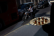 """A biker on a motorbike waits in traffic in Threadneedle Street in the City of London, with a nearby shop employee offering passers-by samples of speciality tea. Sitting on his bike, the rider waits for the lights to change but looks a small version according to the scale of the tray. Threadneedle Street is famous as the site of the Bank of England; the bank itself is sometimes known as 'the Old Lady of Threadneedle Street' and has been based at its current location since 1734. The etymology of the name Threadneedle Street is possibly from the Anglo-Saxon thread meaning """"to prosper""""."""