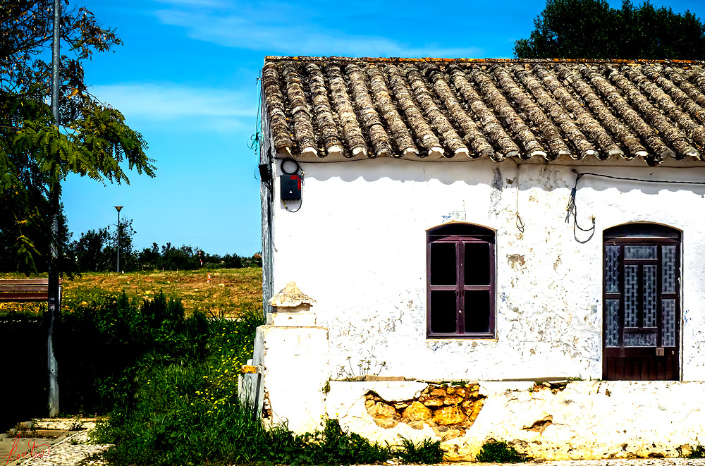 An old building with a decaying wall in front in Tavira, Portugal.