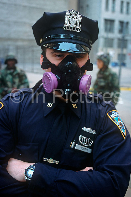 A week after the 9-11 terrorist attacks on the Twin Towers and the Pentagon, an NYPD police officer cop wears a face mask covering nose and mouth - protection from Ground Zero pollutants rumoured to be toxic, on 21st September 2001, New York, USA.