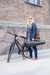 Teenage girl holding violin case with bicycle against brick wall, Munich, Bavaria, Germany