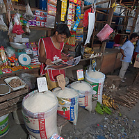 A merchants sells rice & other goods in an outdoor market in upper Belem, a crowded neighborhood in Iquitos, Peru.