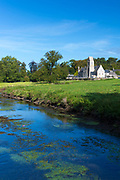Ancient typical Norman church by the river at Vaux-sur-Aure in Normandy