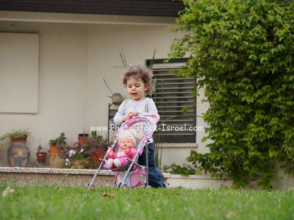 Two year old toddler plays alone outside in the garden