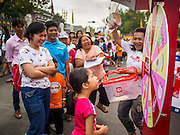 10 JANUARY 2015 - BANGKOK, THAILAND: A girl spins a wheel to win a pastry during Children's Day celebrations at Government House in Bangkok. National Children's Day falls on the second Saturday of the year. Thai government agencies sponsor child friendly events and the military usually opens army bases to children, who come to play on tanks and artillery pieces. This year Thai Prime Minister General Prayuth Chan-ocha, hosted several events at Government House, the Prime Minister's office.    PHOTO BY JACK KURTZ