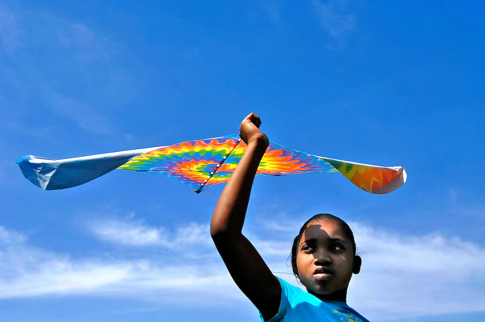 """Why won't mine fly?"""" Tynesha Green, 9, asks the skies over the Douglass Park ball field, already crowded with colorful kites.<br /> <br /> Tynesha and her sister Kanisha, 8, have come with their mentors, Amanda Koellmer and Lauren Smith, volunteers with Big Brothers Big Sisters. They have one mission: to get airborne.<br /> <br /> The first few kites are failures. Toy Story, Elmo and inflatable Winnie the Pooh all crash and burn. Tynesha jogs across the soggy field, the cuffs of her jeans muddy, her arm outstretched to release the string. Each time the kites return to earth, her spirits deflate a little more.<br /> <br /> After a consultation with a local kite-flying expert, Tynesha revives her quest with another new kite. She names it """"Tie-Dye"""" for its spiral of rainbow colors. """"Tie-Dye, you're going to be the best flier ever,"""" Tynesha says.<br /> <br /> Tynesha runs across the outfield, dodging younger children and jumping over kite strings. From the outfield to the infield, from the infield to the basketball courts, Tynesha is determined to fly, but the winds are not cooperating.<br /> <br /> """"You guys hungry? Ready to leave?"""" Amanda asks. The girls are discouraged. They look at each other. """"I want to try one more time,"""" Tynesha says.<br /> <br /> With the wind at her back she catches a breeze, and """"Tie-Dye"""" lifts into the Saturday afternoon sky. Tynesha jumps. She screams. She's flying.<br /> <br /> After a short minute, """"Tie-Dye"""" comes back to earth, but the girls are energized by their victory. They get a second wind, a third, a fourth and then the inevitable. """"Tie-Dye"""" is caught high in the branches of a tree. As they try to retrieve it, the string snaps and the colorful kite becomes impossible to reach.<br /> <br /> Kanisha collects her own kite. Empty-handed, Tynesha follows Lauren and Amanda back to the parking lot, shedding tears for """"Tie-Dye,"""" now trapped in flight forever."""