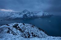 Hiker on winter summit of Offersøykammen mountain peak with Flakstadøy in background, Lofoten Islands, Norway