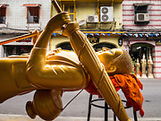 """12 NOVEMBER 2012 - BANGKOK, THAILAND:   A statue of the Buddha in front of a shop on Bamrung Muang Street in Bangkok. Thanon Bamrung Muang (Thanon is Thai for Road or Street) is Bangkok's """"Street of Many Buddhas."""" Like many ancient cities, Bangkok was once a city of artisan's neighborhoods and Bamrung Muang Road, near Bangkok's present day city hall, was once the street where all the country's Buddha statues were made. Now they made in factories on the edge of Bangkok, but Bamrung Muang Road is still where the statues are sold. Once an elephant trail, it was one of the first streets paved in Bangkok. It is the largest center of Buddhist supplies in Thailand. Not just statues but also monk's robes, candles, alms bowls, and pre-configured alms baskets are for sale along both sides of the street.    PHOTO BY JACK KURTZ"""