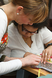 Carer assisting person with Cerebral Palsy and visual impairment in craft activity at a resource for people with physical and sensory impairment.