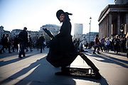 An entertainer dressed up as a witch pretend to be floating in the air.  A large number of performers earn their money outside the national Gallery and the trade is good on a sunny day.