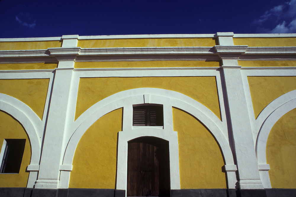 View from the inside courtyard of El Morrow Castle in Old San Juan, Puerto Rico. The interior walls are painted yellow with white arch moulding over wooden doorways and windows with a blue sky in the background.
