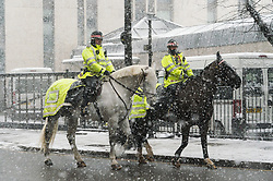 © Licensed to London News Pictures. 28/02/2018. London, UK. Two City of London policemen on horses ride around the City of London as heavy snowfall hits central London at lunchtime. The cold spell named The Beast From The East is due to last a few days. Photo credit: Ray Tang/LNP