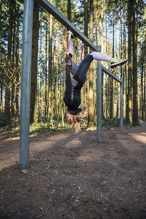 Fit young woman using gymnastic rings on fitness trail