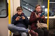 Commuters on the London Underground, check their mobile phone on 26th February 2017 in London, United Kingdom. From the series Our Small World, an observation of our mobile phone obsessions