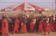 Husa Islamic militias dressed in Muslim colors parade under a Coca-Cola parasol during the Fantasia Durbar at Kano..The Durbar Fantasia, is the moment where The Husa residents of Kano wear traditional dress, their local leaders and chiefs mount horses, and together with their militias display allegiance and homage to their leader, the Emir of Kano. This takes place after Ramadan. The Emir is Kano's State official political and economic feudal leader, everyone seeks to be in his pleasure, otherwise they reap the consequences..Kano is the largest Muslim Husa city, under the feudal, political and economic rule of the Emir. Kano and the other eleven northern states are under Islamic Sharia Law which is enforced by official state apparatus including military and police, Islamic schools and education, plus various volunteer Militia groups supported financially and politically by the Emir and other business and political bodies. 70% of the population live below the poverty line. Kano, Kano State, Northern Nigeria, Africa