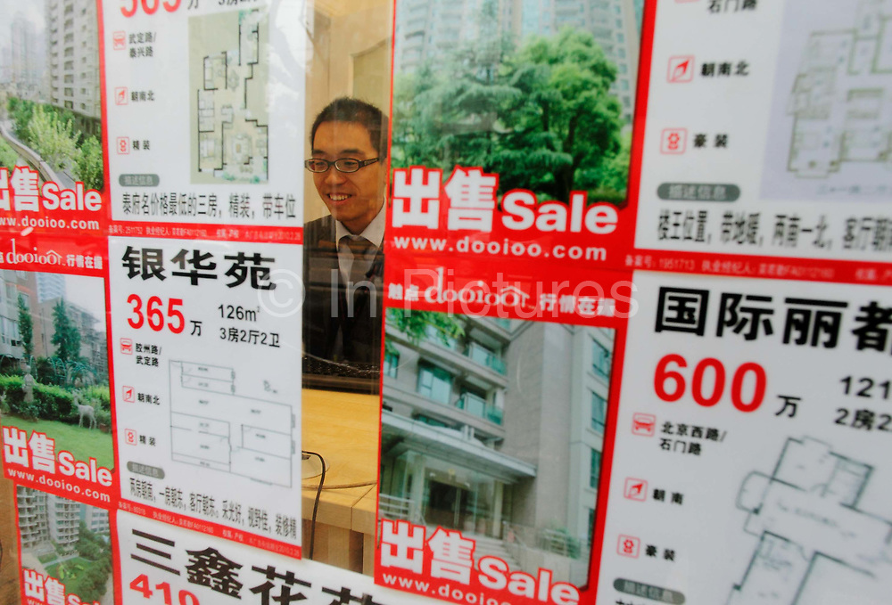 An agent works behind his desk in a real estate agency with a window displaying housing units for sale  in Shanghai, China on 10 December, 2009.  Despite repeated efforts by government to rein in housing prices, housing in major cities in Shanghai and Beijing have changed little from their peaks  and the flow of hot money into smaller cities have fueled additional bubbles.