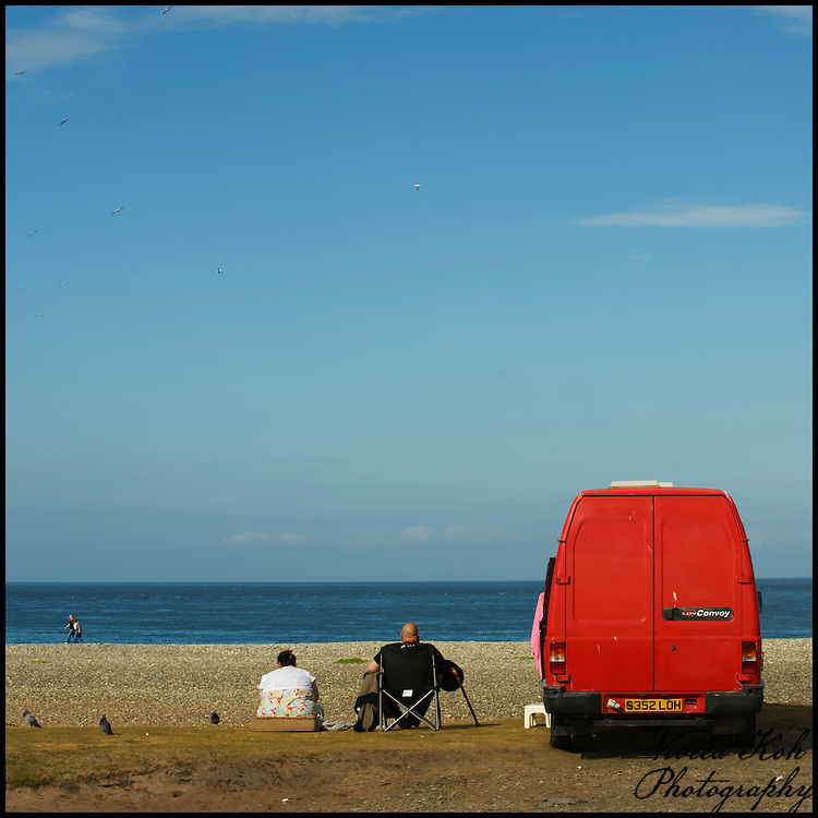 Couple on beach with red van