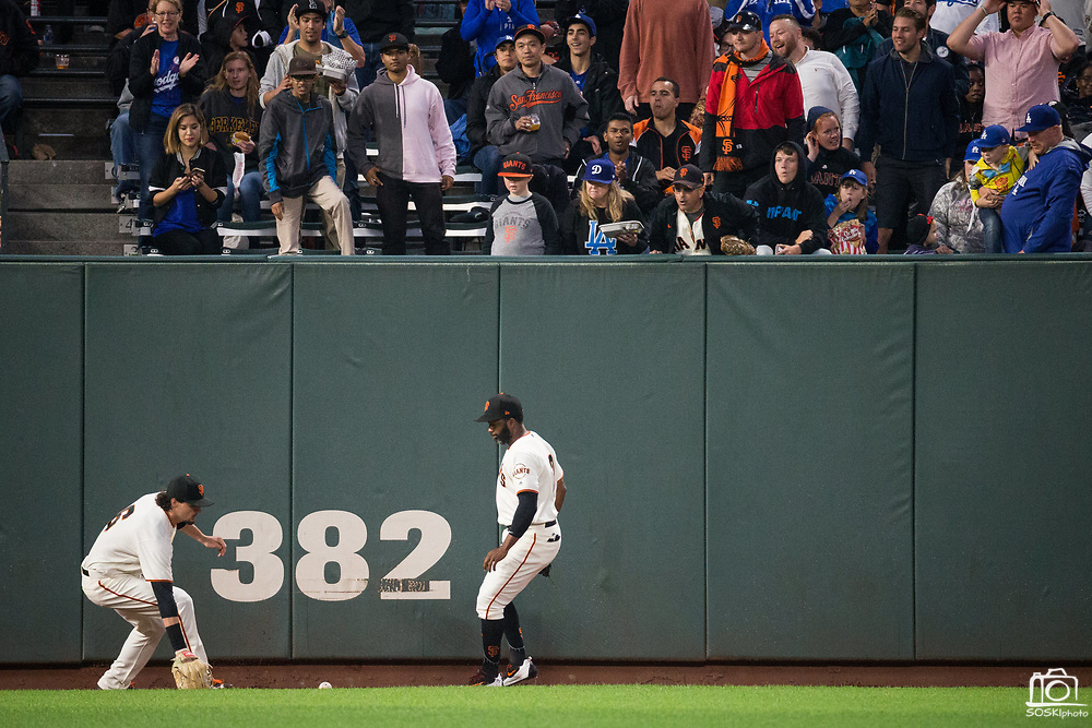 San Francisco Giants left fielder Jarrett Parker (6) and San Francisco Giants center fielder Denard Span (2) chase down a Los Angeles Dodgers hit at the warning track at AT&T Park in San Francisco, California, on September 13, 2017. (Stan Olszewski/Special to S.F. Examiner)