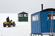 A fisherman drives an All-Terrain-Vehicle across a frozen lake to his ice fishing hut during a snowstorm.