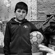 Unidentified boy with football. Potosi. Bolivia..Sitting at 4,090M (13,420 Feet) above sea level the small mining community of Potosi, Bolivia is one of the highest cities in the world by elevation and sits ?sky high? in the hills of the land locked nation. Overlooking the city is the infamous mountain, Cerro Rico (rich mountain), a mountain conceived to be made of silver ore. It was the major supplier of silver for the spanish empire and has been mined since 1546, according to records 45,000 tons of pure silver were mined from Cerro Rico between 1556 and 1783, 9000 tons of which went to the Spanish Monarchy. The mountain produced fabulous wealth and became one of the largest and wealthiest cities in Latin America. The Extraordinary riches of Potosi were featured in Maguel de Cervantes famous novel Don Quixote. One theory holds that the mint mark of Potosi, the letters PTSI superimposed on one another is the origin of the dollar sign. Today mainly zinc, lead, tin and small quantities of silver are extracted from the mine by over 100 co-operatives and private mining companies who still mine the mountain in poor working conditions, children are still used in the mines and the lack of protective equipment and constant inhalation of dust means miners have a short life expectancy with many contracting silicosis and dying around 40 years of age. UNESCO designated the historic city a World Heritage site in 1987. Most of Potosí's colonial churches have been restored, and tourism has increased. Potosi, Bolivia. 16th September 2011. Photo Tim Clayton