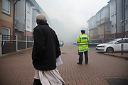 London, UK. Wednesday, May 18th 2016. Local residents look on as Fire Crew tackle a fire in a block of flats in Brodlove Lane in Wapping, London, United Kingdom.