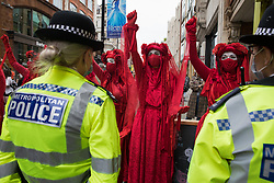 Members of the Extinction Rebellion Red Rebel Brigade raise clenched fists in front of Metropolitan Police officers in the Covent Garden area during the first day of Impossible Rebellion protests on 23rd August 2021 in London, United Kingdom. Extinction Rebellion are calling on the UK government to cease all new fossil fuel investment with immediate effect. (photo by Mark Kerrison/In Pictures via Getty Images)