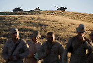 Two M1-A1 Abrams tanks sit atop a nearby hill next to an Assault Amphibious Vehicle as Marines from the 2nd Battalion, 5th Marine Regiment go over the days' battle plans at Camp Pendleton.