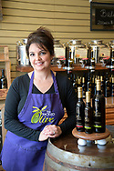Carolyn Hill, owner of the Sacred Olive oil and vinegar store, stands next to a display at her location in Winter Garden, Fla., Sunday, Feb. 5, 2017. (Phelan M. Ebenhack via AP)