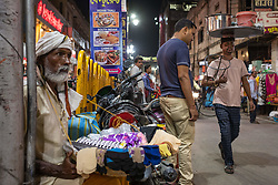 May 18, 2019 - Varanasi, India - On 17 May 2019, a street merchant sits on a busy pedestrian passage, selling small items to people in the city of Varanasi, India. (Credit Image: © Diego Cupolo/NurPhoto via ZUMA Press)