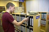 young student researching in the local records office, Lancashire pulling book