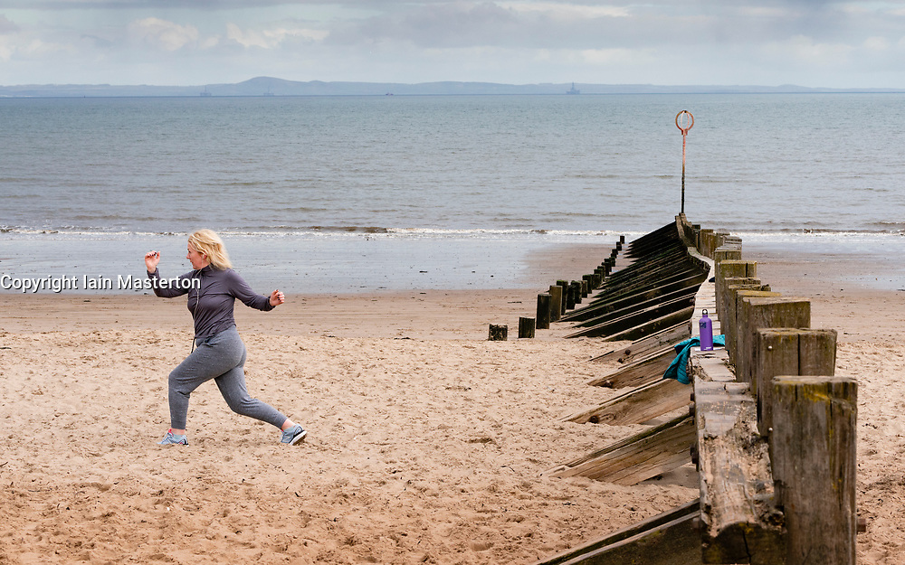 Portobello, Scotland, UK. 28 March, 2020. On the first weekend of the coronavirus lockdown the public were outdoors exercising and maintaining social distancing along Portobello beachfront promenade. Pictured; Annabel Meikle from Portobello working out on her special covid-19  solo training program set by her personal trainer. Iain Masterton/Alamy Live News