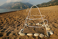 At Cirali Beach the nests of the Loggerhead Sea Turtles (Caretta caretta) are caged by volunteers which guard the beach at night. Leaflets inform tourists and local people not to disturb or destroy the nests by digging or setting up sun umbrellas.
