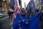 Anti Brexit pro Europe demonstrator screams in anger in protest waving European Union and Union Jack flags and placards in Westminster opposite Downing Street on the day the Prime Minister takes her draft Brexit deal to gain backing from her cabinet in Westminster on 14th November 2018 in London, England, United Kingdom.