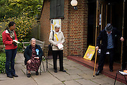 As an elderly man exits a Parish hall, three tellers from the main political parties check the addresses of voters in St. Barnabas Parish Church, Dulwich Village SE21 that serves as a temporary Polling station for voters on Britain's general election day. Their job is to record the election numbers of those about to vote, making sure that their political colleagues don't drop more literature in to that address, now that the occupants have voted.