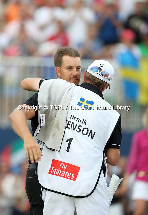 Henrik STENSON (SWE) wins on 18th with his caddie Gareth Lord (ENG) during fourth round DP World Tour Championship 2013,Jemeirah Golf Estates, Dubai,UAE.