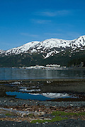 """..The strangest town in Alaska, Whittier - only reachable by tunnel or ship. It's a stop off point for Cruise ships, and the Alaska raildroad. 90% of inhabitants live in one building! Originally established as a military base during World War two.....Reflection in sea water pool, Whittier, Alaska, destination for cruisee ships. The large square building you can see is the Buckner Building,  - """"A city under one roof"""". Built in 1953, this derelict building was abandoned but can't be demolished due to the amount of asbestos inside. It was damaged by earthquake in  1964."""