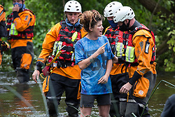 Denham, UK. 24 July, 2020. A police officer from Hampshire Police Marine Support Unit pushes a female activist from HS2 Rebellion from the river Colne where she had been trying to hinder the destruction of an ancient mature alder tree in connection with works for the HS2 high-speed rail link in Denham Country Park. A large policing operation involving the Metropolitan Police, Thames Valley Police, City of London Police and Hampshire Police as well as the National Eviction Team was put in place to enable HS2 to remove the tree.