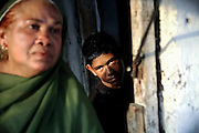 Asif, 14, (right) a boy suffering from a severe neurological disorder, is standing near his home in the impoverished Arif Nagar Colony in Bhopal, Madhya Pradesh, India, near the abandoned Union Carbide (now DOW Chemical) industrial complex.