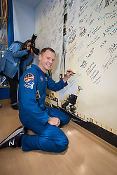 At the Baikonur Cosmodrome Museum in Kazakhstan, Expedition 57 crewmember Nick Hague of NASA signs a mural Oct. 6 as part of traditional pre-launch activities. Hague and Alexey Ovchinin of Roscosmos will launch Oct. 11 from the Baikonur Cosmodrome on the Soyuz MS-10 spacecraft for a six-month mission on the International Space Station.<br /> <br /> NASA/Victor Zelentsov