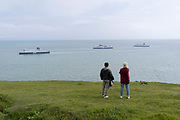 Two walkers watch departing and arriving cross-Channel ferries near Dover Docks,  along the clifftop footpath, near the edge of Englands iconic White Cliffs, under threat from chalk and soil erosion, on 27th July, at Langdon Bay, Dover, in Kent, England.