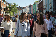 Crowds of visitors arrive coming down the hill past the colourfully painted house fronts on Portobello Road in Notting Hill, West London, England, United Kingdom. People enjoying a sunny day out hanging out at the famous Sunday market, when the antique stalls line the street.  Portobello Market is the worlds largest antiques market with over 1,000 dealers selling every kind of antique and collectible. Visitors flock from all over the world to walk along one of Londons best loved streets.